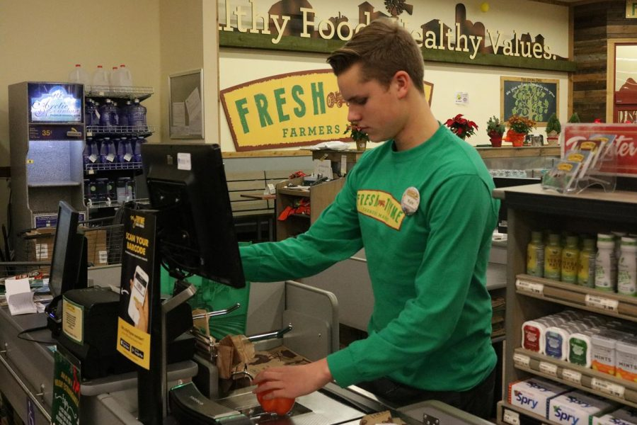 Fresh+Thyme+worker+and+high+school+student+Kyle+Hedblom+working+his+shift+after+school+on+Dec.+4.+Fresh+Thyme+Farmers+Market+currently+employs+multiple+students%2C+including+Hedbolm.