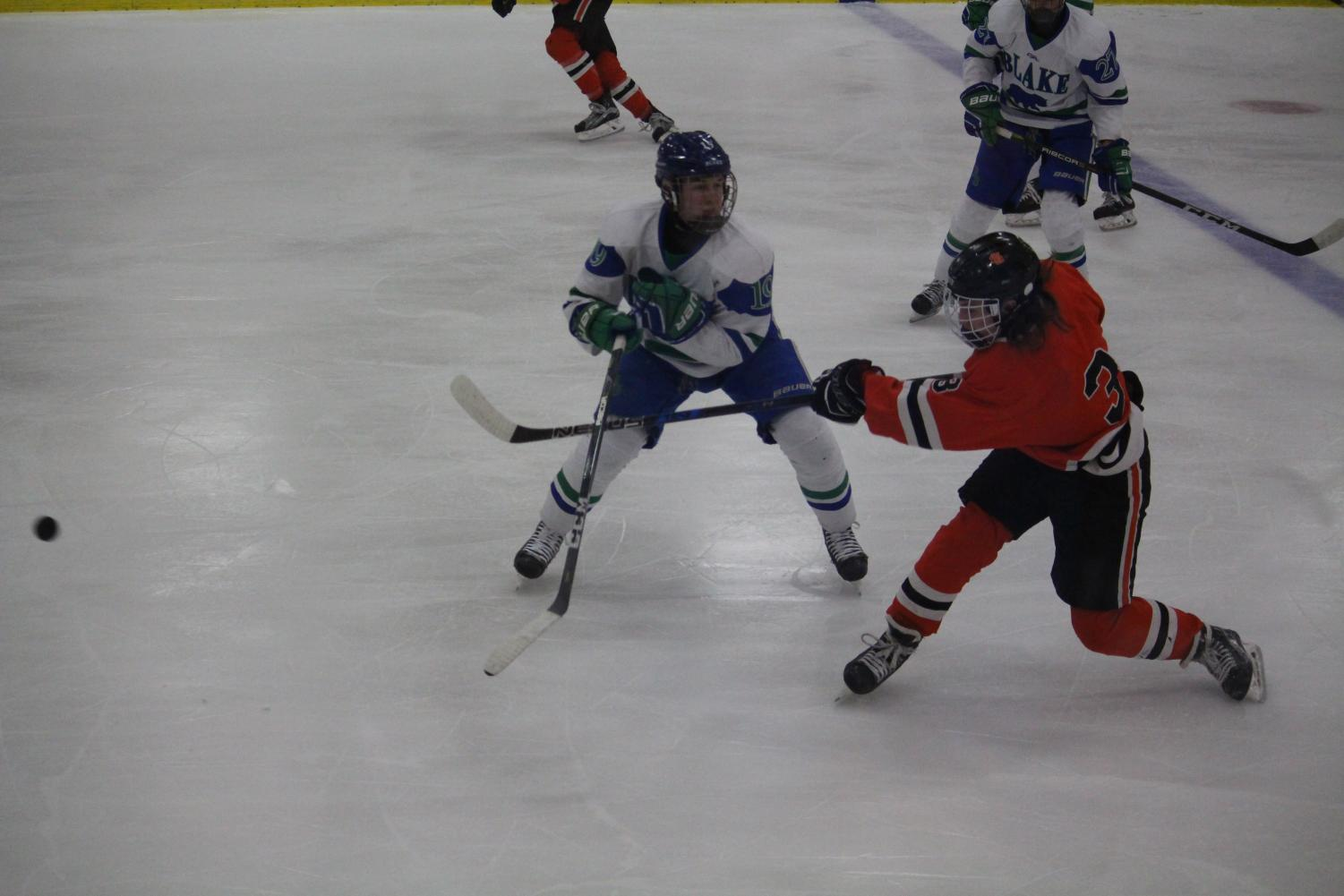 Junior Jackson Hand passes the puck to one of his teammates during their game Jan 11 against Blake. Hand said the team's schedule remains the same over finals.