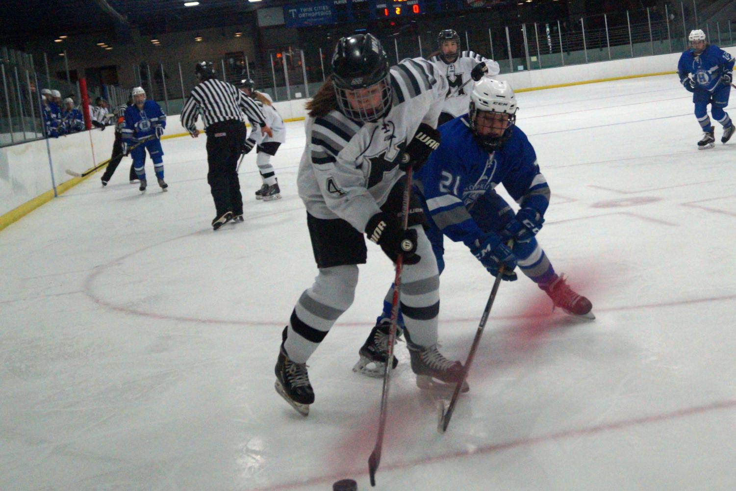 Sophomore Sarah Mccallon fights for the puck against Edina defender. Girls hockey plays Wayzata at 3 p.m. Feb 6 at the Minnetonka A arena.