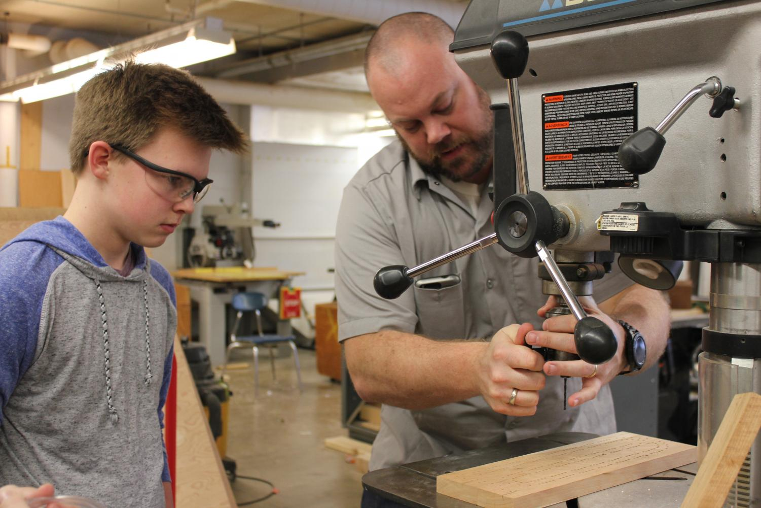 Head of the art technology department Trevor Paulson helps a student in woodworking class Jan. 25. Paulson received the TIES 2017 Technology Leadership and Exceptional Teacher Award.