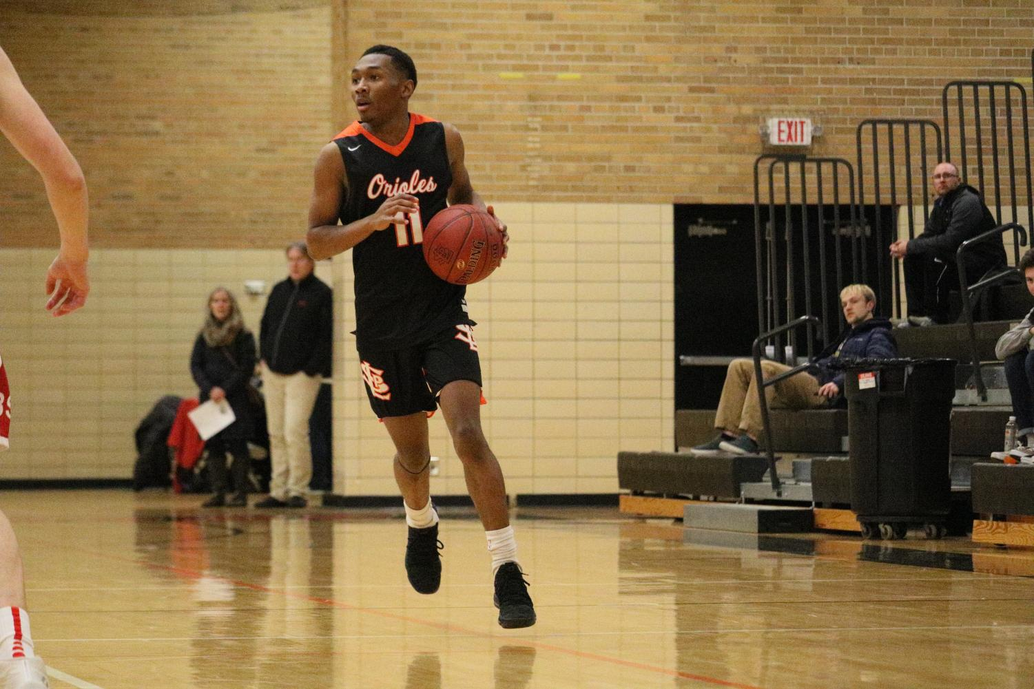 Senior Cire Mayfield dribbles down the court in the Orioles win over Benilde Jan. 30. Mayfield is ten points away from his 1000th career point. Mayfield will look to make history as the Orioles play 7 p.m. Feb. 9 at the high school against Chaska.