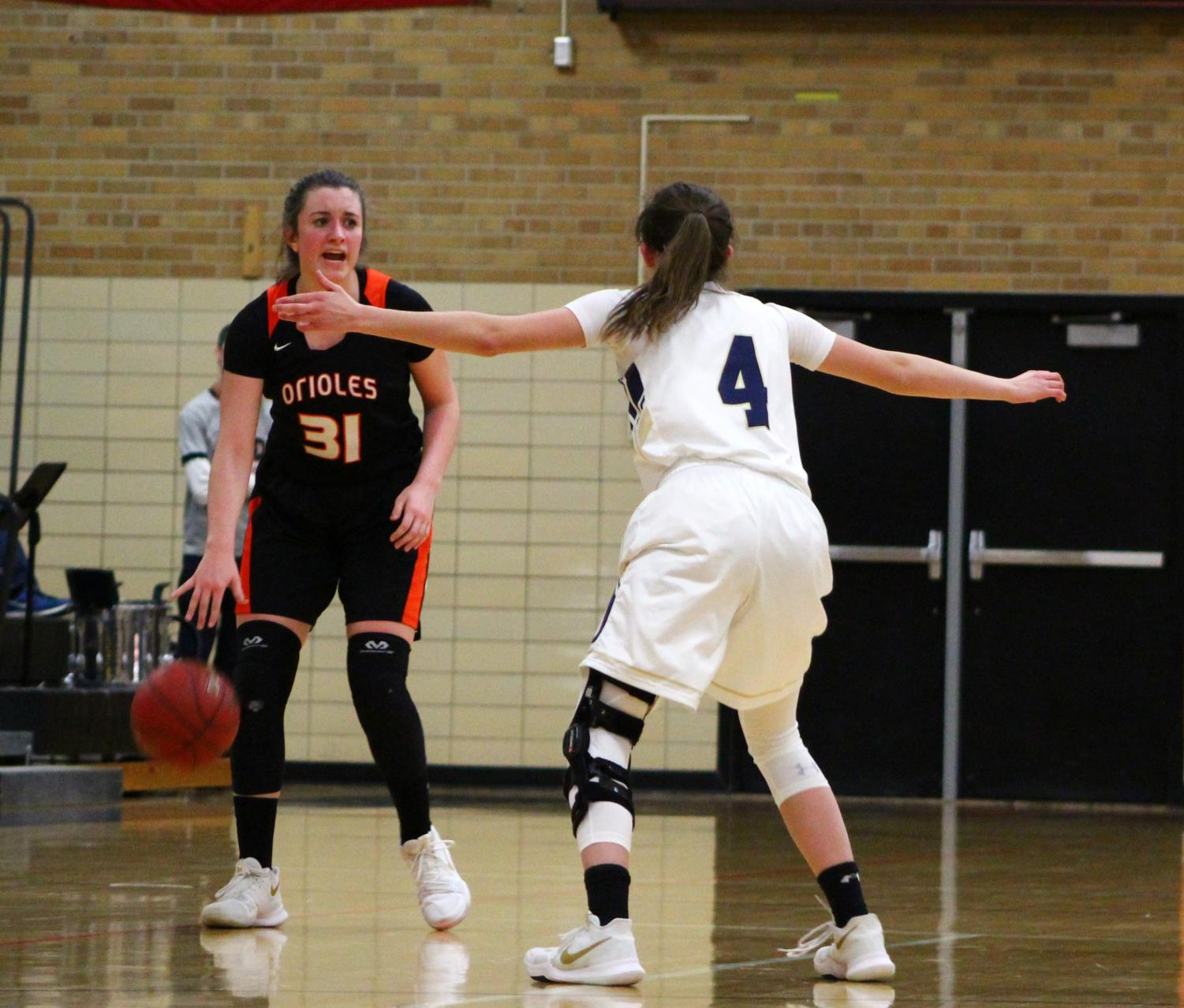 Sophomore Shayla Miller scans the court for open team mates while dribbling down the court on Feb 5. The Orioles lost 58-63 to Chanhassen.