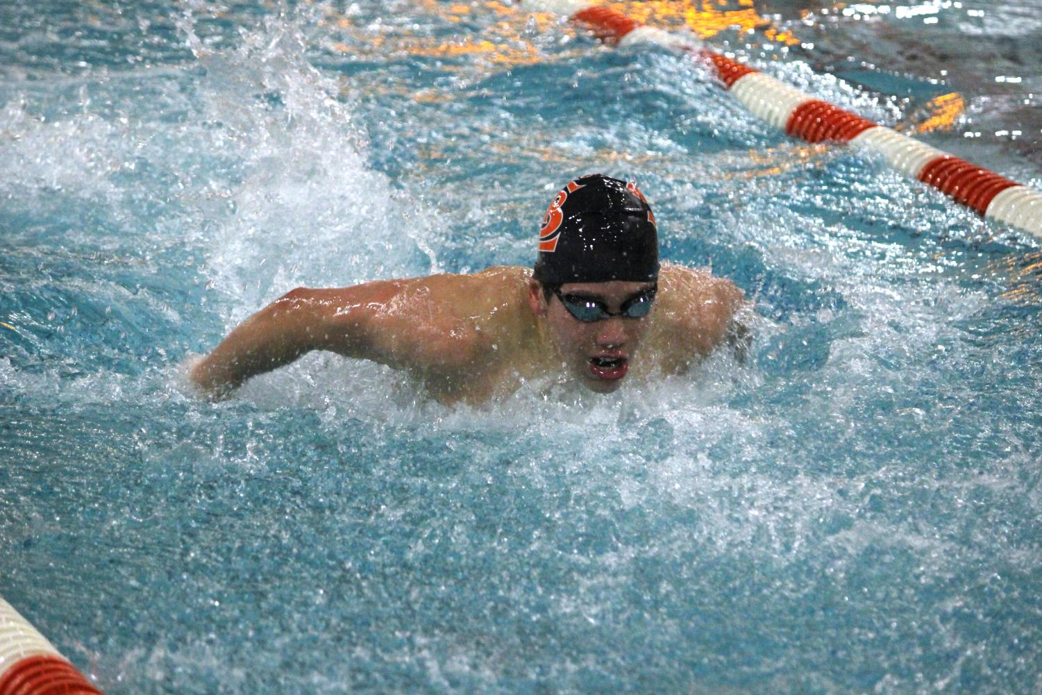 Freshman Hayden Zheng competes in his race during senior night, the final home meet of the season against Benilde on Feb. 2. Hayden broke the 100 backstroke pool record previously held by Chaska-Chan with a time of 00:53.85.