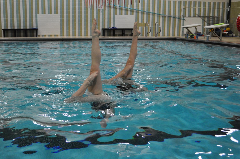 Senior Savannah Kjaer and sophomore Annie Breyak practice their vertical bent knees at a Minnesota Aquafins club practice. They practice three days a week to prepare for the upcoming high school season.