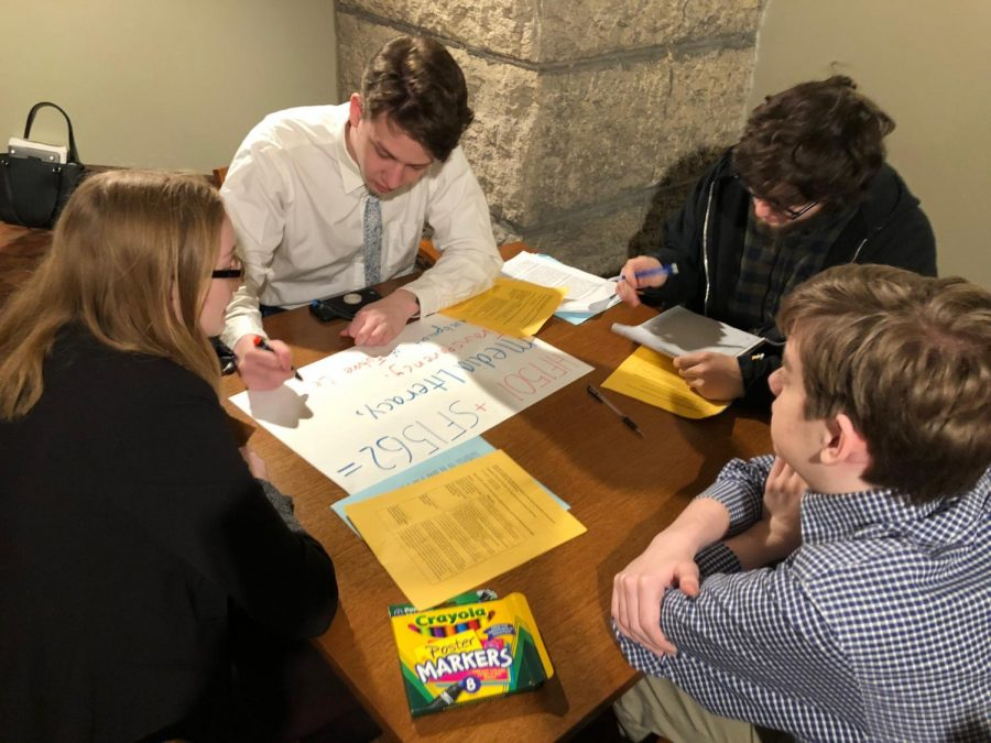 Senior Lukas Levin and other supporters of the New Voices of Minnesota create signs advocating for the protection of student journalist voices. Students worked on the signs before entering the Senate Chamber March 19.