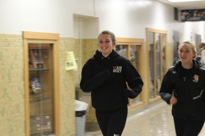 Junior track captain Anna Jennisen runs during practice warm ups March 21.