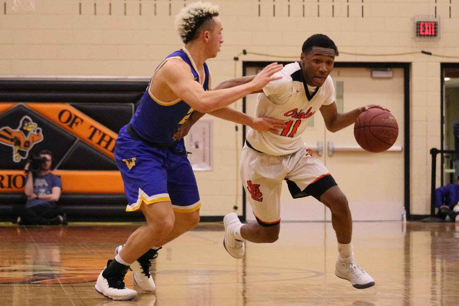 Senior Cire Mayfield drives to the basket against Wayzata defender Kody Williams. The Orioles were defeated by the Trojans 66-59 Mar. 9.