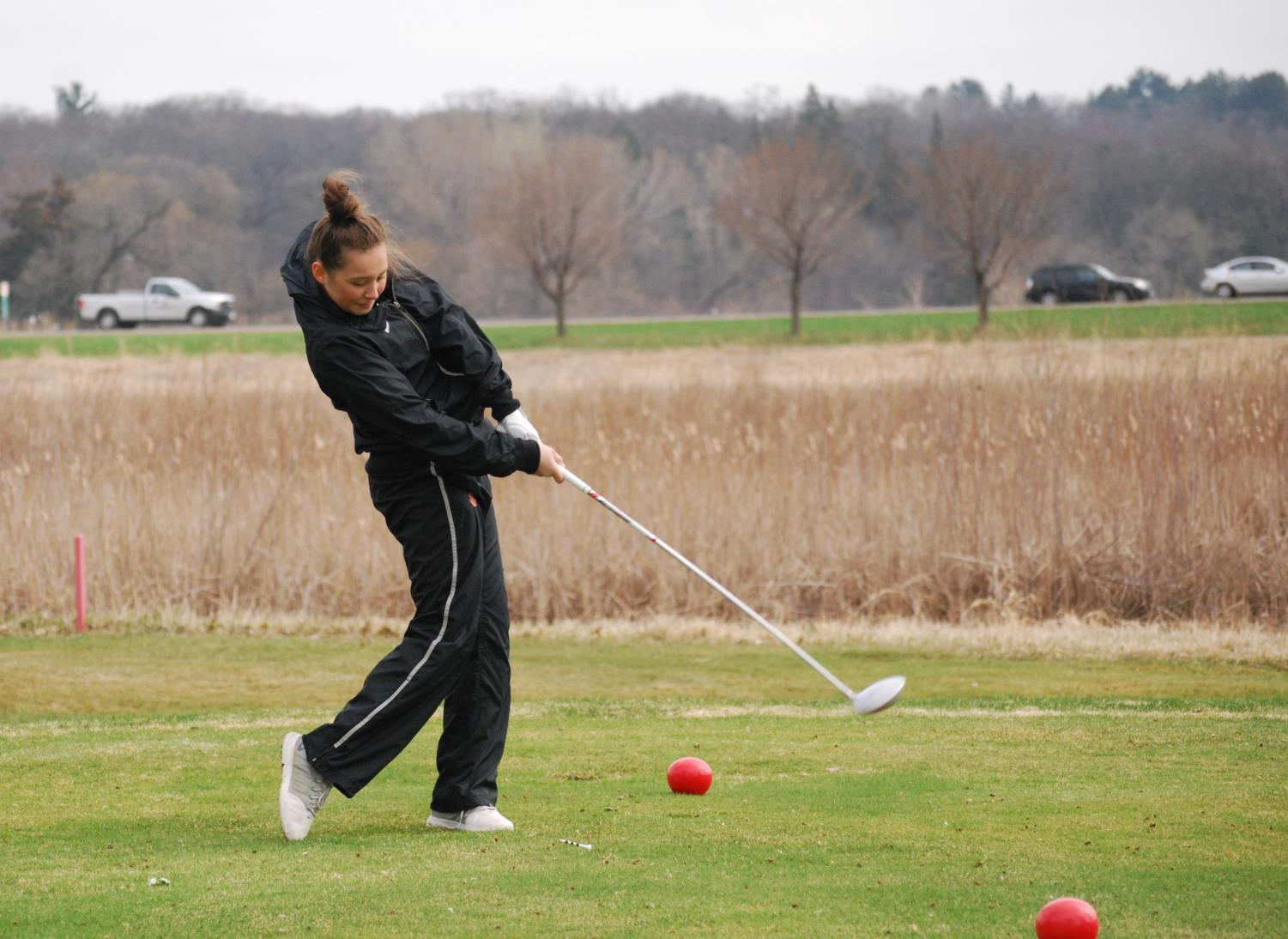 Freshman Izzy Segal hits the ball during a golf match at Theodore Wirth Park.