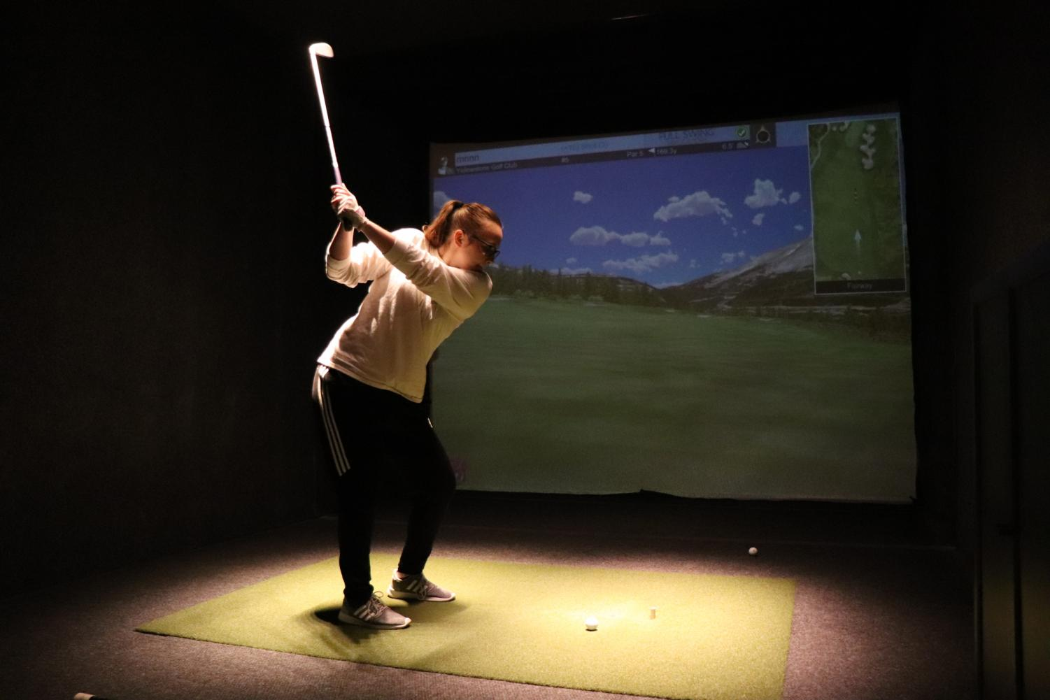 Girls' golf captain senior Carly Livingston practices her swing indoors at the Life Time Fitness in Park. The teams has been practicing indoors due to the cold weather.