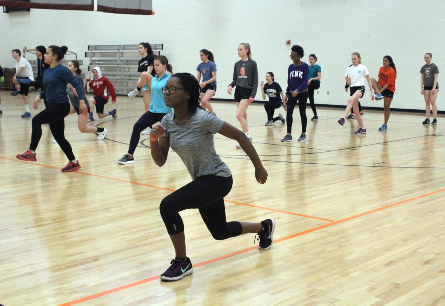 Sophomore Hilda Habia lunges at the beginning of practice April 13. Athletes warm up inside due to the weather.