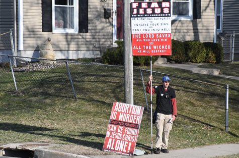 Anti-abortion protester Jeffery Stocker stands outside the high school on the corner of Edgewood and 33rd St. April 24.