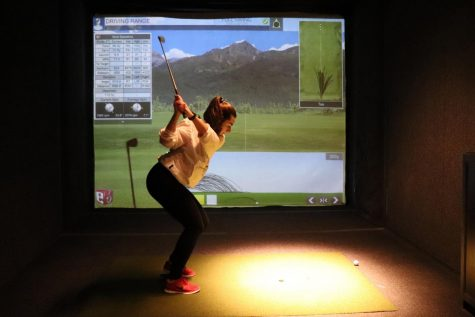 Junior Rachel Salzer practices her swing at golf practice April 12. The team has been practicing indoors at the St. Louis Park Lifetime Fitness due to cold weather.