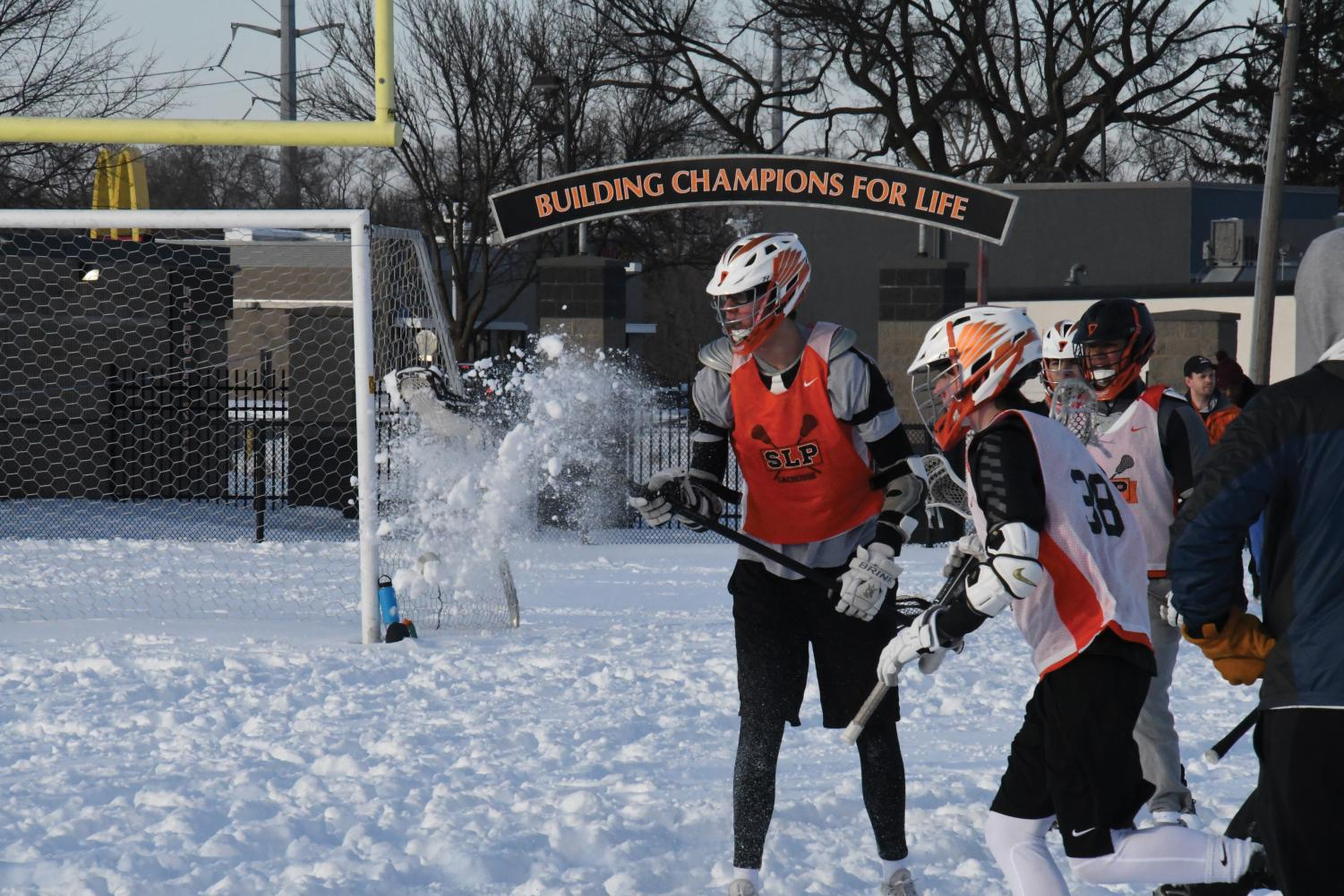 Senior Caleb Mesick scoops the ball out of the snow to toss it to his fellow teammates during boys' lacrosse practice April 4 at the stadium. Spring sports have had difficulties practicing outdoors because of a reported 9 inches of snow, according to Minnesota CBS.