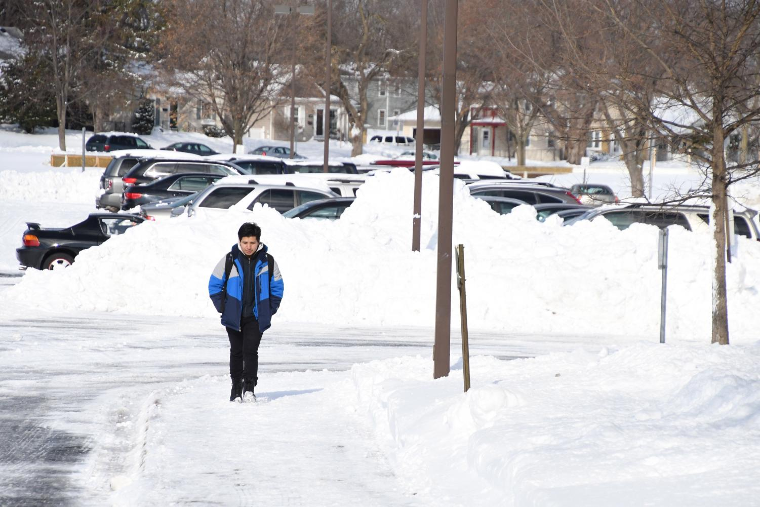 Senior Wilson Tamay Pineda walks through the snow into school April 16. Over the weekend St. Louis Park received roughly 17 inches of snow causing several surrounding districts to cancel school.
