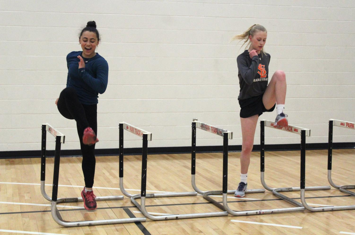 Senior girls' track captain Anna duSaire and sophomore Anna Keith jump over hurdles April 13. Athletes warm up during practice.