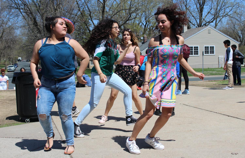 Juniors Natalia Caraballo and Esmeralda Perez perform a cultural dance at the Cinco de Mayo celebration during lunch May 4.