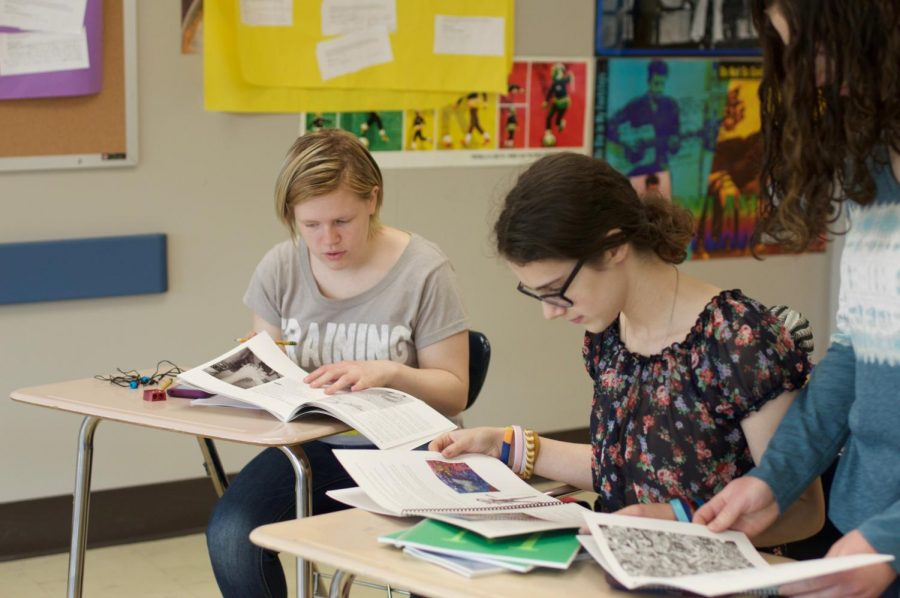 Seniors Ciara Woida and Chava Buchbinder along with junior Nechama Buchbinder look over previous years' 36 Arts books.