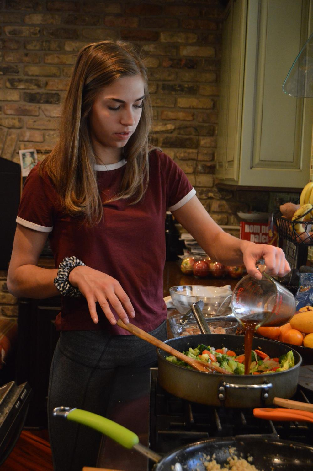 Senior Hannah Wolk prepares a cauliflower shrimp stir fry May 2. Wolk and her family previously participated in the Whole30 challenge, during which participants eliminate sugar, alcohol, grains, legumes, soy, and dairy from their diets for 30 days. Although they no longer keep a strict paleo diet, Wolk and her family still eat many paleo foods.