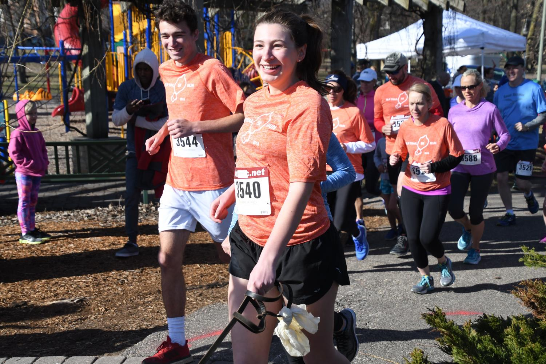 Junior Libby Ramsburger runs with her dog alongside fellow classmate Ben Klepfer during the 5k run held on April 29.