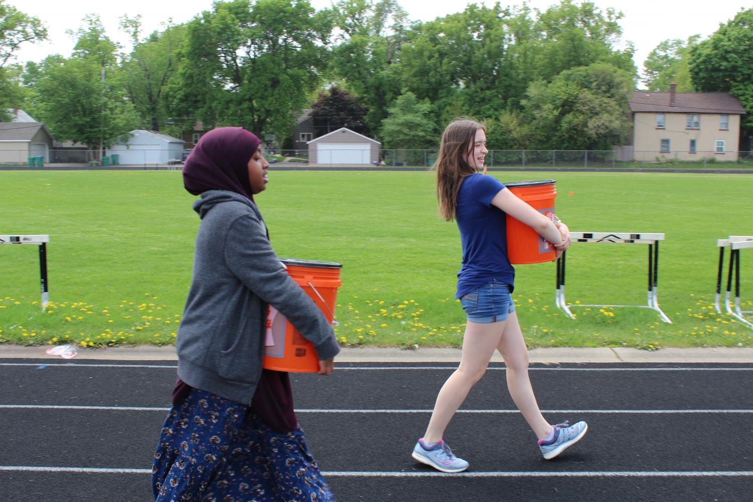 Freshmen Iqra Abdi and Courtney Hanson carry five-gallon buckets of water around the track as part of a scarcity simulation in their Civics/Economics class May 22.