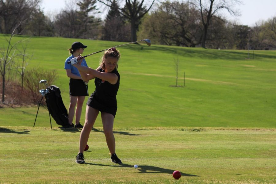 Sophomore Lily Rostal prepares to hit a golf ball during a match against Benilde St. Margaret's. The event took place May 4 at the Dwan Golf Course.