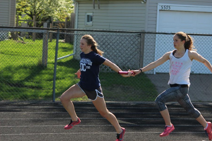 Junior+Anna+Jenson+practices+grabbing+the+baton+from+her+partner+sophomore+Sidney+Hayenga+during+a+track+practice.+