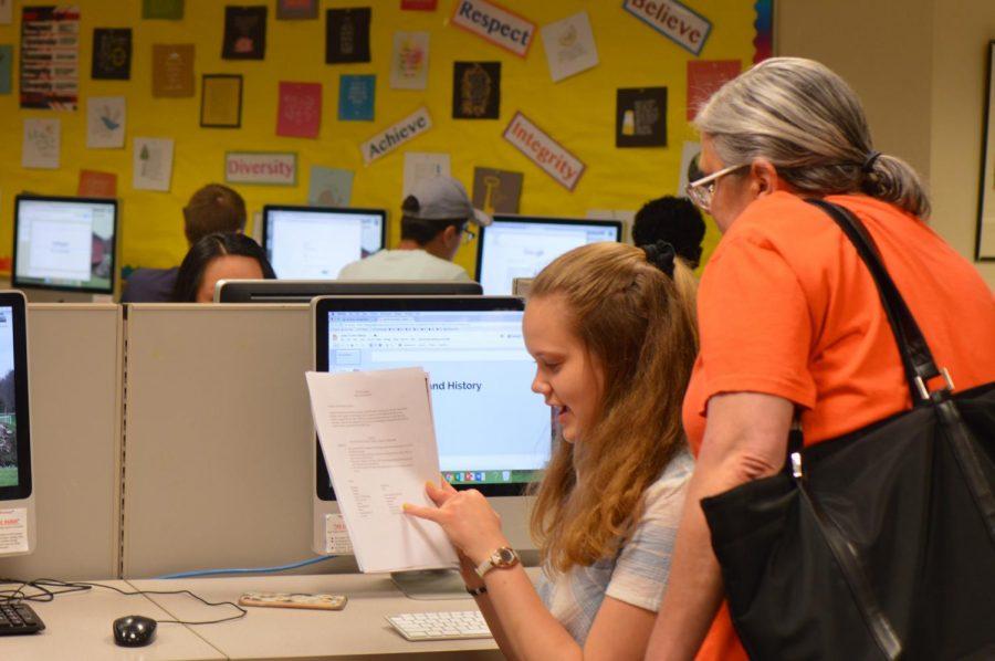 Teacher+Deb+Skadden+assists+sophomore+Isabel+Kjaer+with+an+AP+World+history+assignment.