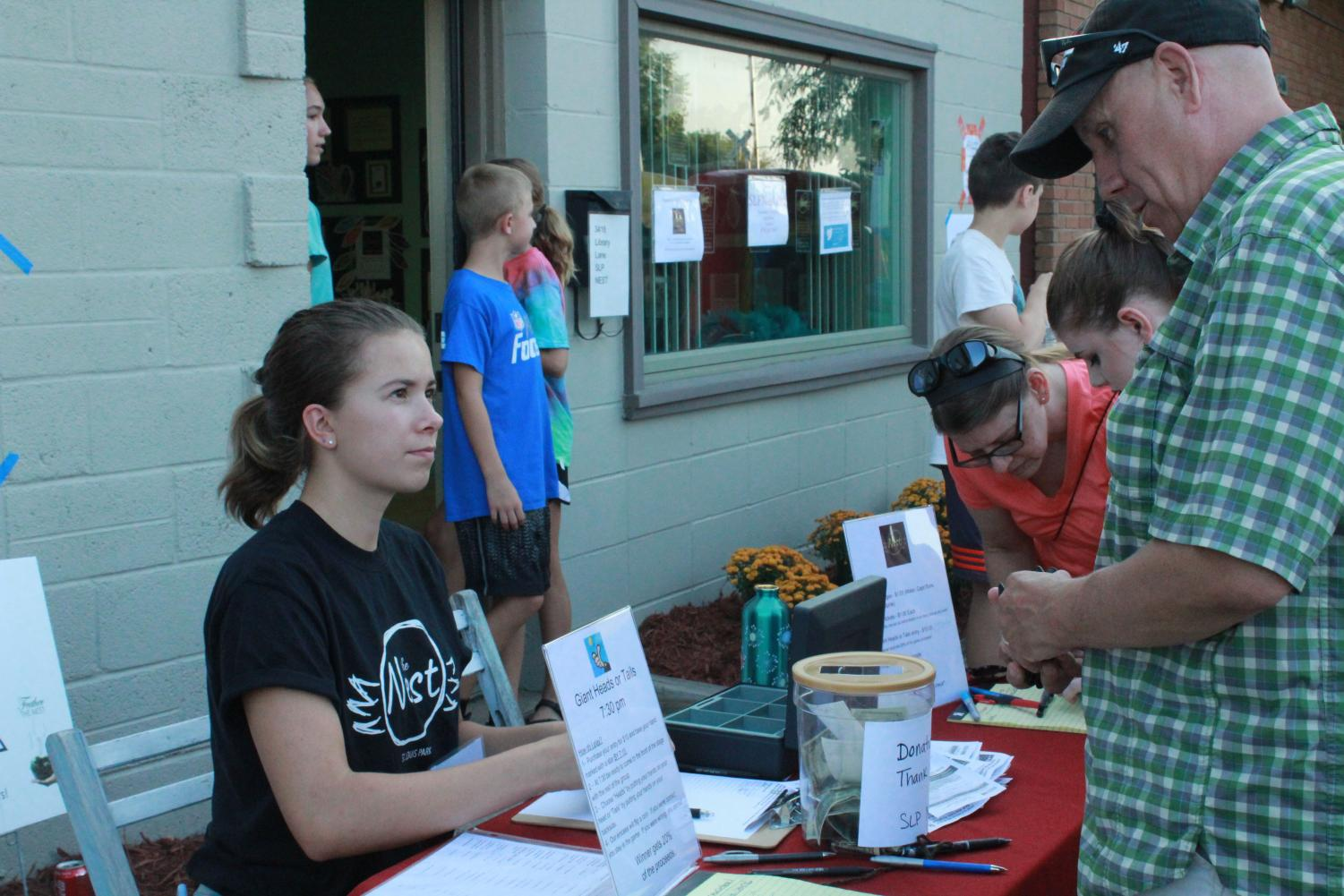 Senior and SLP Nest board member Lexi Lee sells raffle tickets to a community member at the SLP Nest street party Aug. 15. All money and donations collected at the event will be used support and run the SLP Nest.
