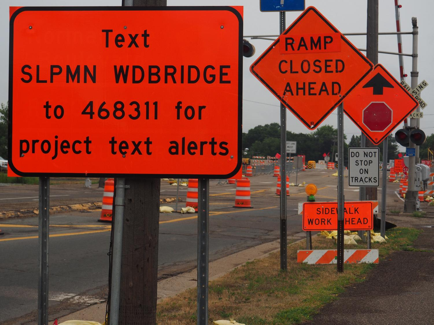 Signs and cones distract drivers on Wooddale Bridge. The bridge construction causes traffic buildup and confusion with many new signs and driving precautions.