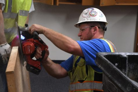 A construction worker uses a saw to take a handle off a door at the high school Aug. 20. District improvements will be completed by 2022, according to District facilities manager Tom Bravo.