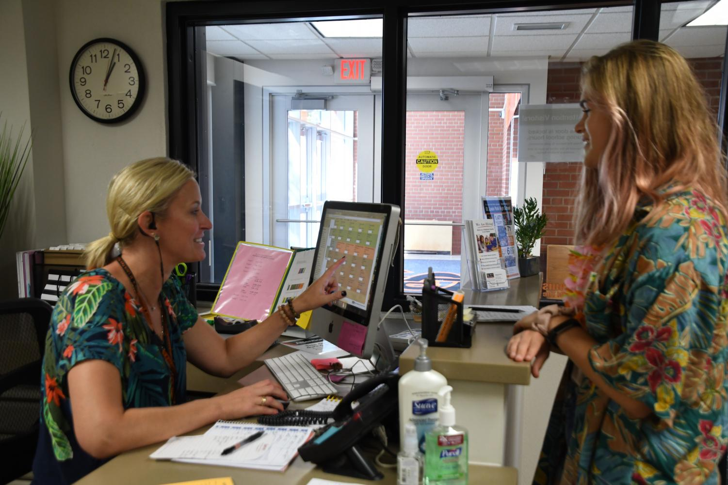Senior Sophia Davenport jokes with administrator Jennifer Thomas in the student office. According to Assistant Principal Jessica Busse, only seniors are able to leave the school during lunch and they need to return through the student office or cafeteria showing their student ID.