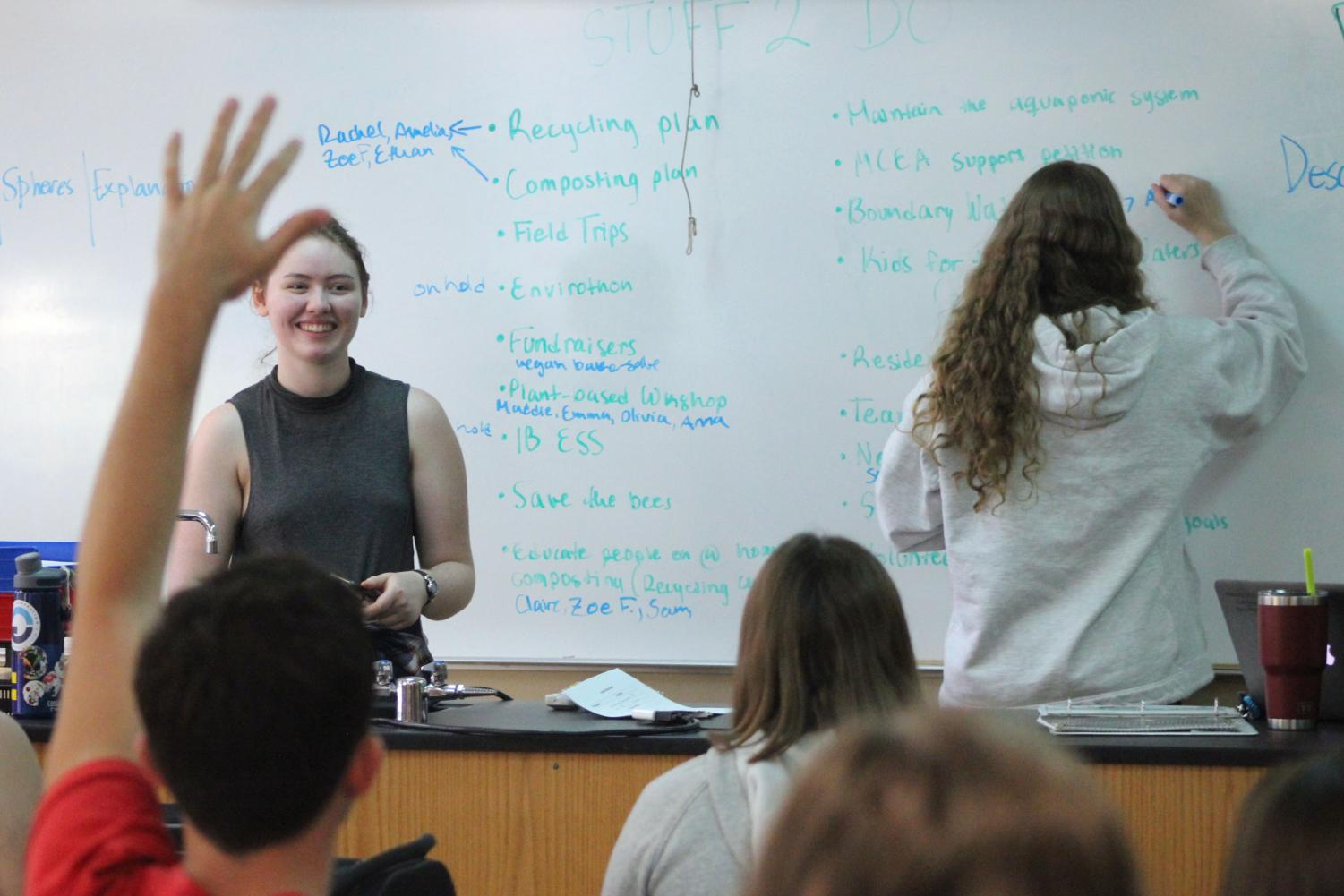 Senior Roots and Shoots president Katie Christiansen works with club members to organize what they plan to do this year.