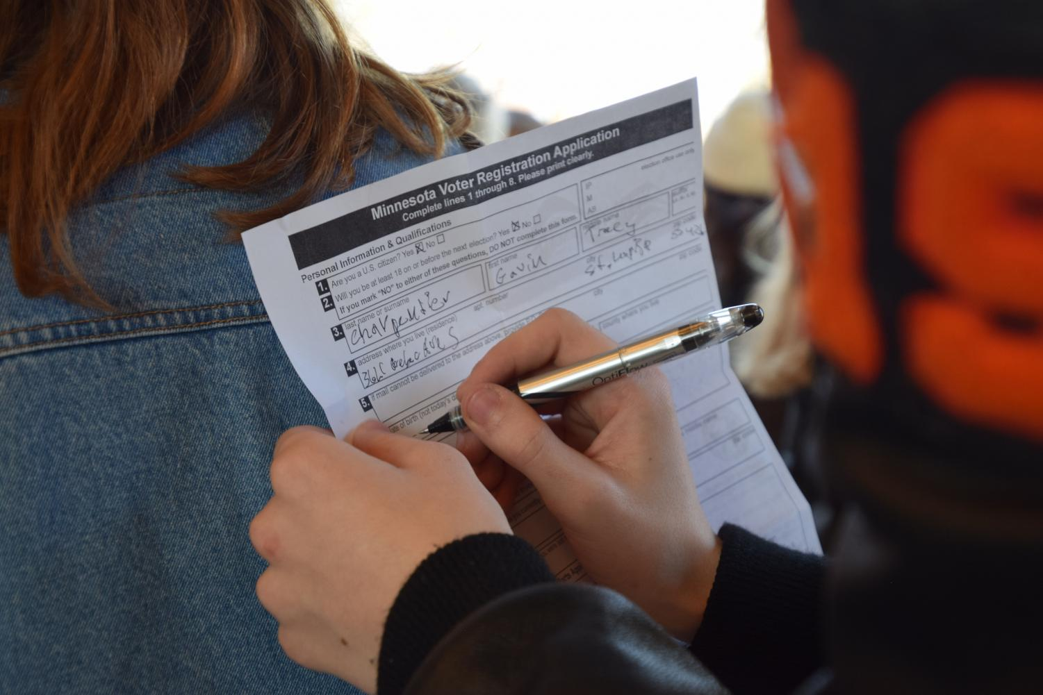 Senior Gavin Carpentier signs a voter registration application during the national high school walkout last year on March 14. ACT SLP is leading a voter registration assembly Sept. 26 to encourage eligible seniors to register to vote for the elections in November.