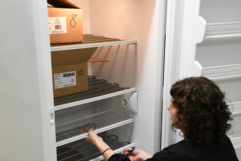 DECA adviser Sophia Ross removes frozen pizzas during distribution Oct. 25.