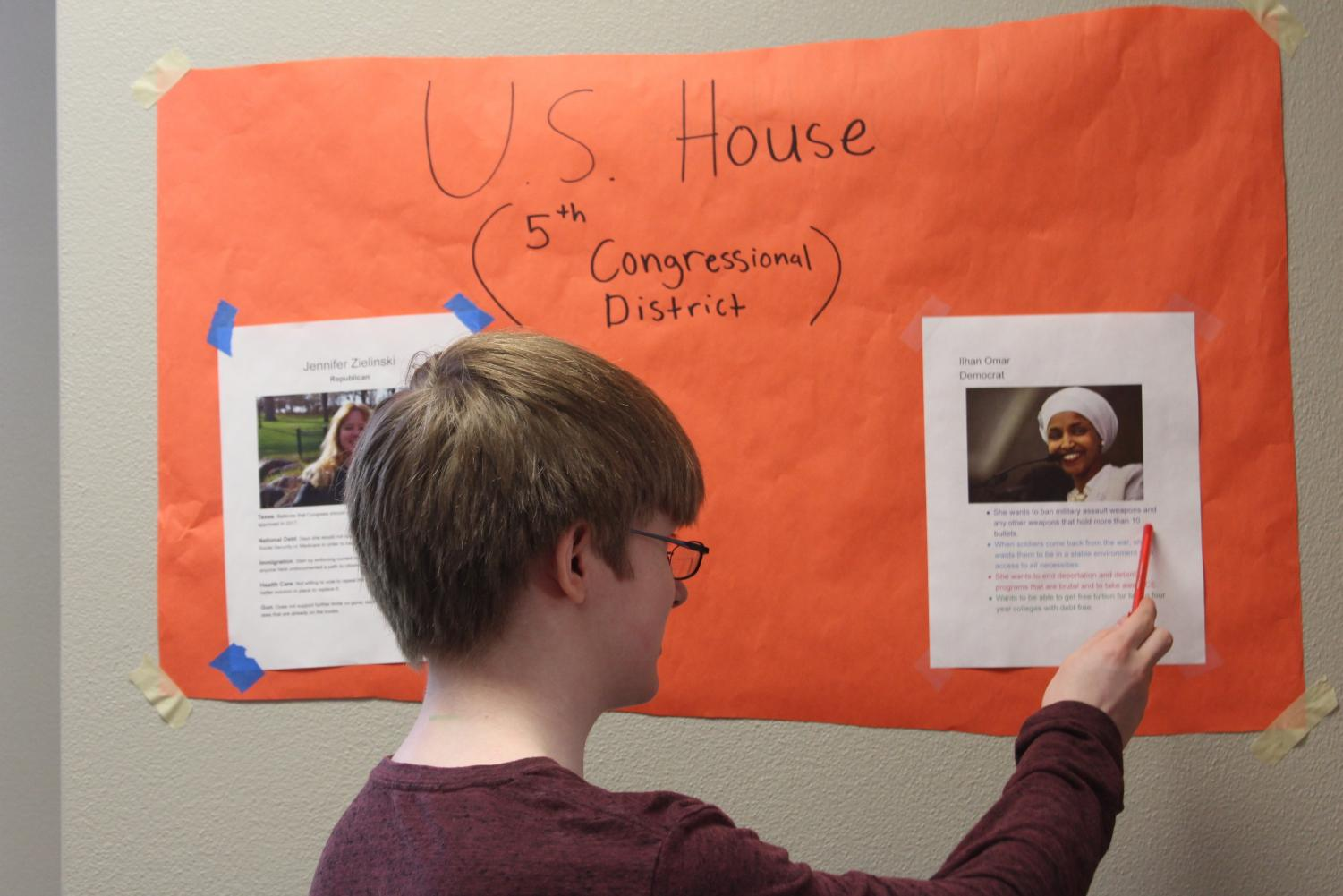 Sophomore Joseph McIndoo learns about NTA club poster encouraging students to vote. Several more Posters are hung up around the high school cafeteria.