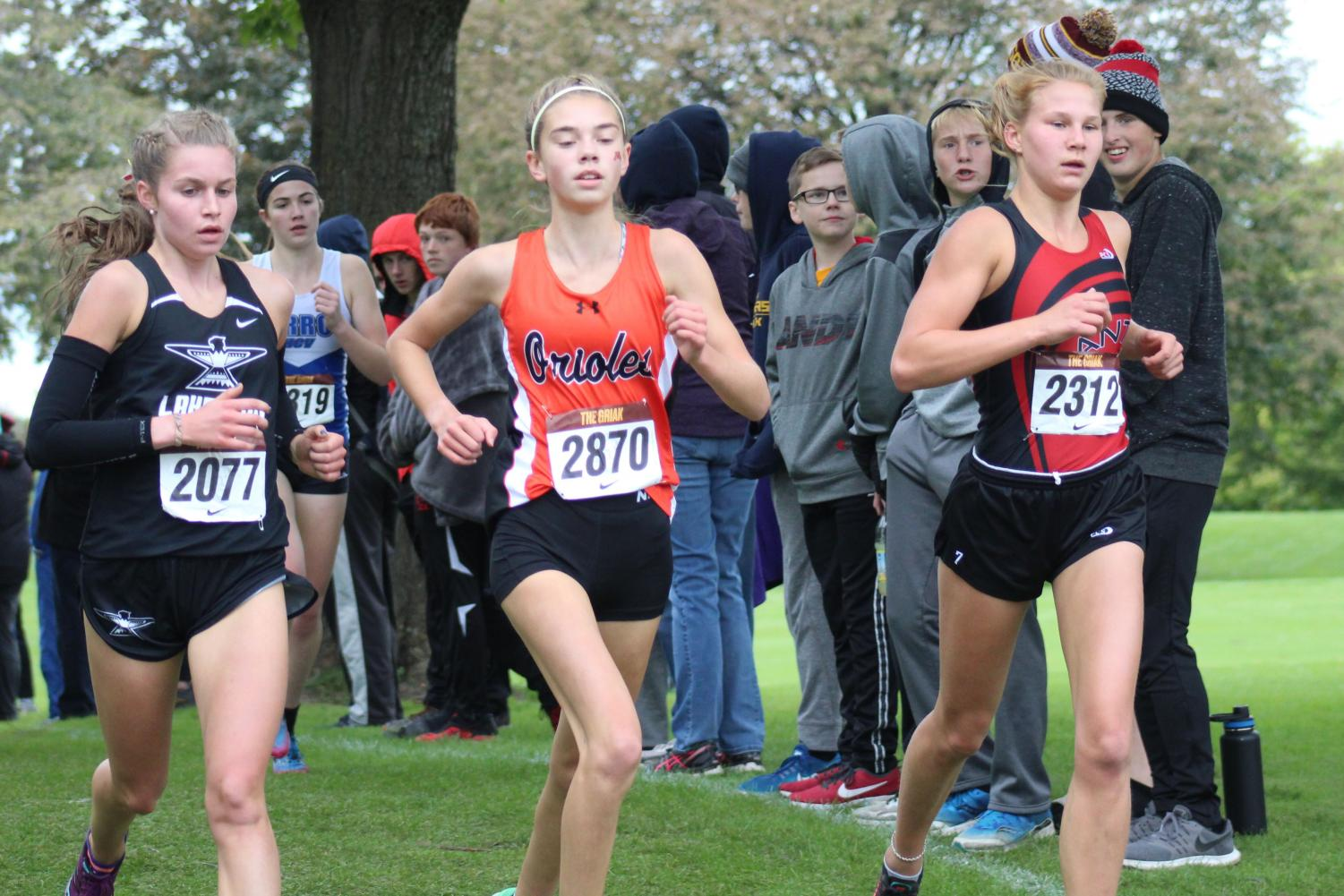 Freshman Josie Mosby runs with two competitors in the Griak race, Sept. 29. Mosby placed first individually and the team placed first overall.