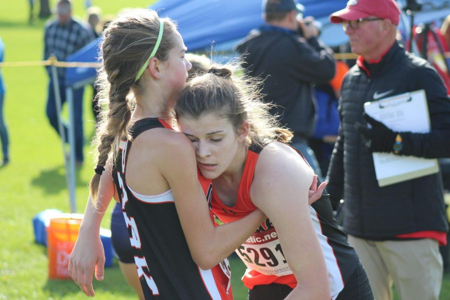 Freshman Josie Mosby holds up sophomore Erin Brousseau after a race Oct. 16. Both are exhausted after the strenuous run.