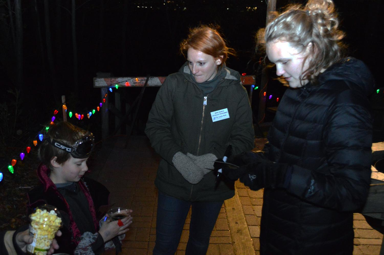 Senior NHS public relations officer Ilsa Olsen signs off Westwood Hills Nature Center Halloween Party goers for the mini golf course. The event was Oct. 19 and 20.