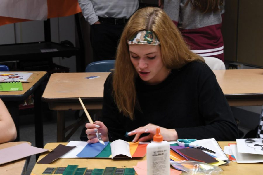 Junior Hattie Kugler glues different colored swatches together to make a collage during her fifth hour mixed media arts Oct. 3. She is making this project for the invitation to the BARR National Conference in April.