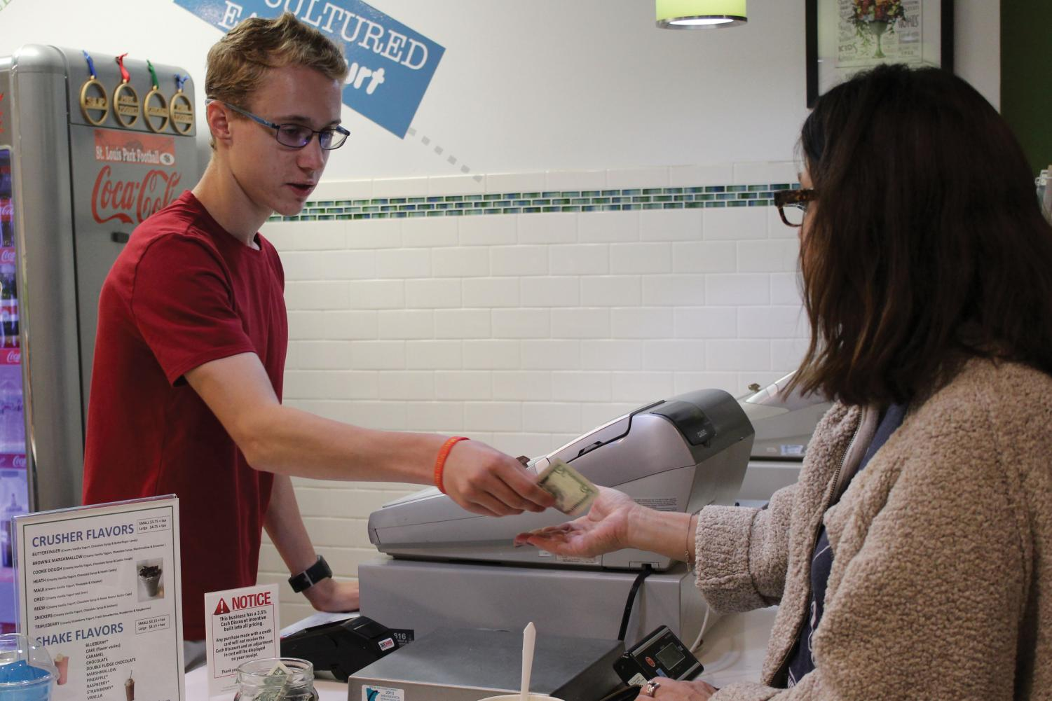 Sophomore Jackson Thoe gives change to a customer at Park Yogurt. The store was in business for four years before its closing.