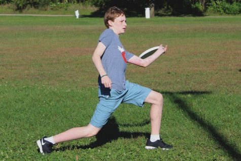 Freshman Cole Blavat throws disc during a warm-up drill at a captain's practice Sep. 24. The boys ultimate team recently started a fall league to get more practice.