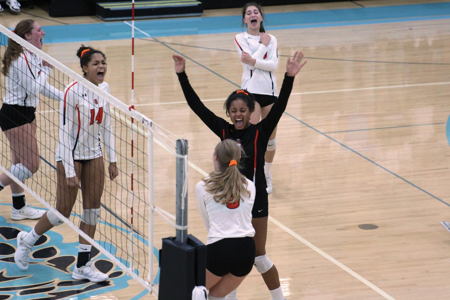 Senior Maddy McIntosh and sophomore Raegan Alexander celebrate with their teammates after winning a point against Bloomington Jefferson Oct. 25. The team moved on to play Edina in the semi-finals on Oct. 30.