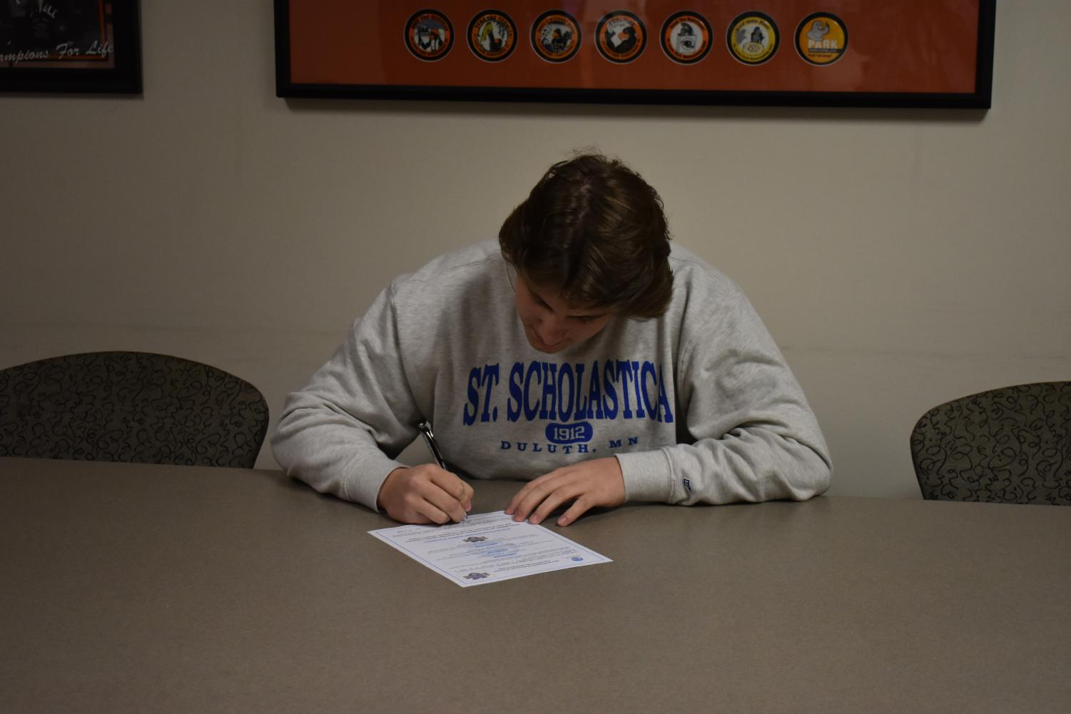 Senior Luke Boyum signs his commitment to the college of St. Scholastica in the athletic office. Boyum was accompanied by his coach, friends and family while he signed.