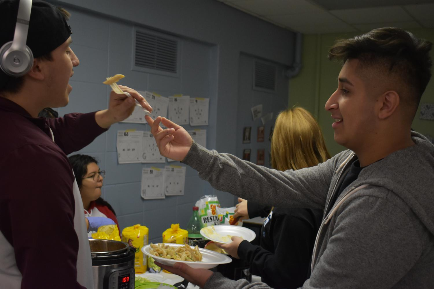Senior Danny Martinez shares food with senior Braulio Vela-Garray during NTA's Thanksgiving meal. The Thanksgiving meal is one example of how NTA creates a tight-knit community within the program.