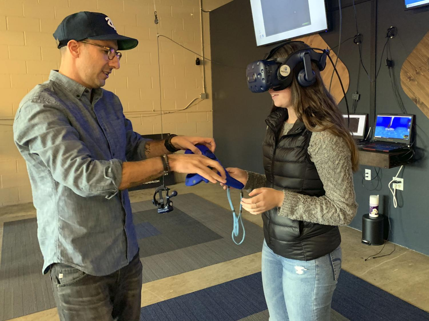Owner of Rem5VR lab, Amir Berenjian helps set up a game of virtual reality fruit ninja.