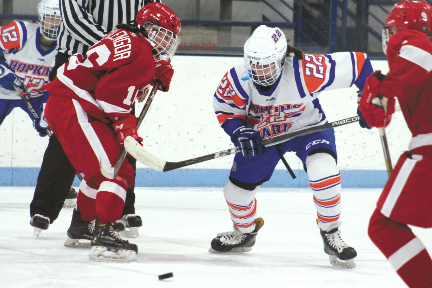 Sophomore Erin Brousseau fights for the puck against Benilde senior Sally Calengor. Its next game will be 7 p.m. Nov. 30 at Minnetonka Ice Arena.