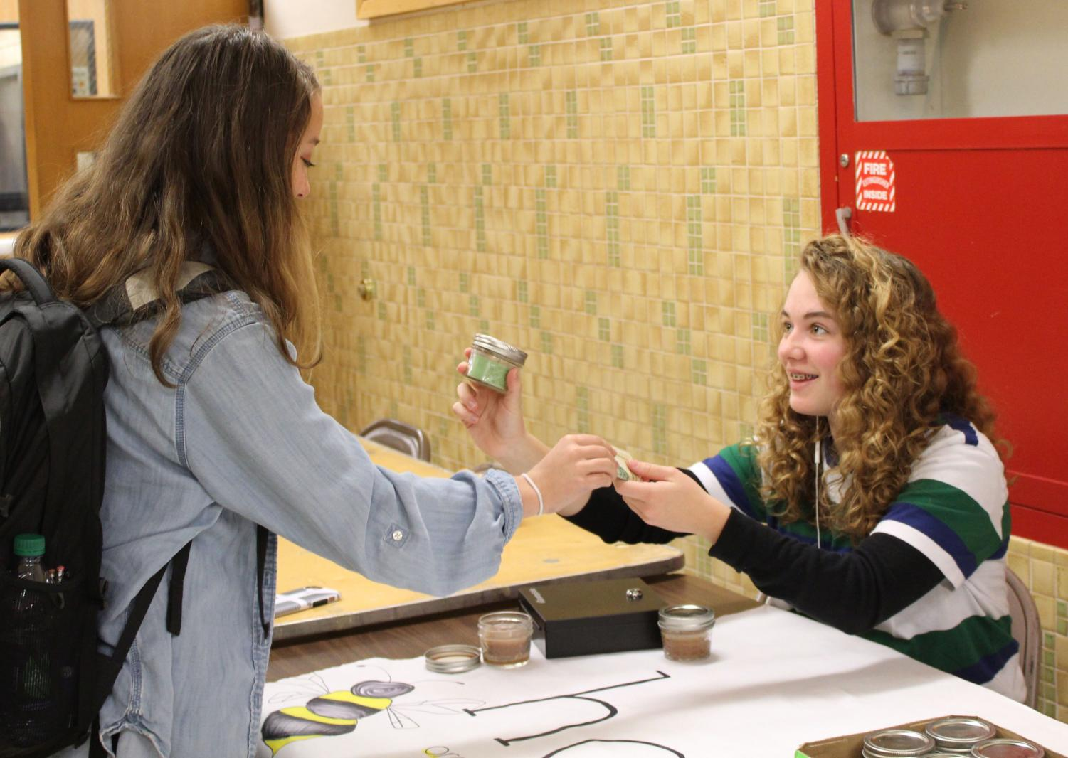 Sophomore Evie Gutzke sells a candle to sophomore Maia Seidel outside the lunch room Nov. 7. The candles are selling for seven dollars .