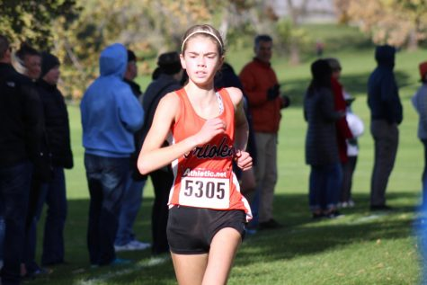 Josie Mosby running close to the finish line placing 20th at State. She received her second best time 18:32.20 Nov 3.