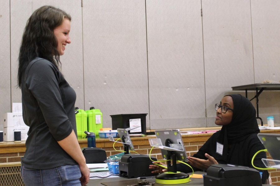 Junior Muna Hussin checks in a voter at the St. Louis Park Middle School polling station Nov 6.