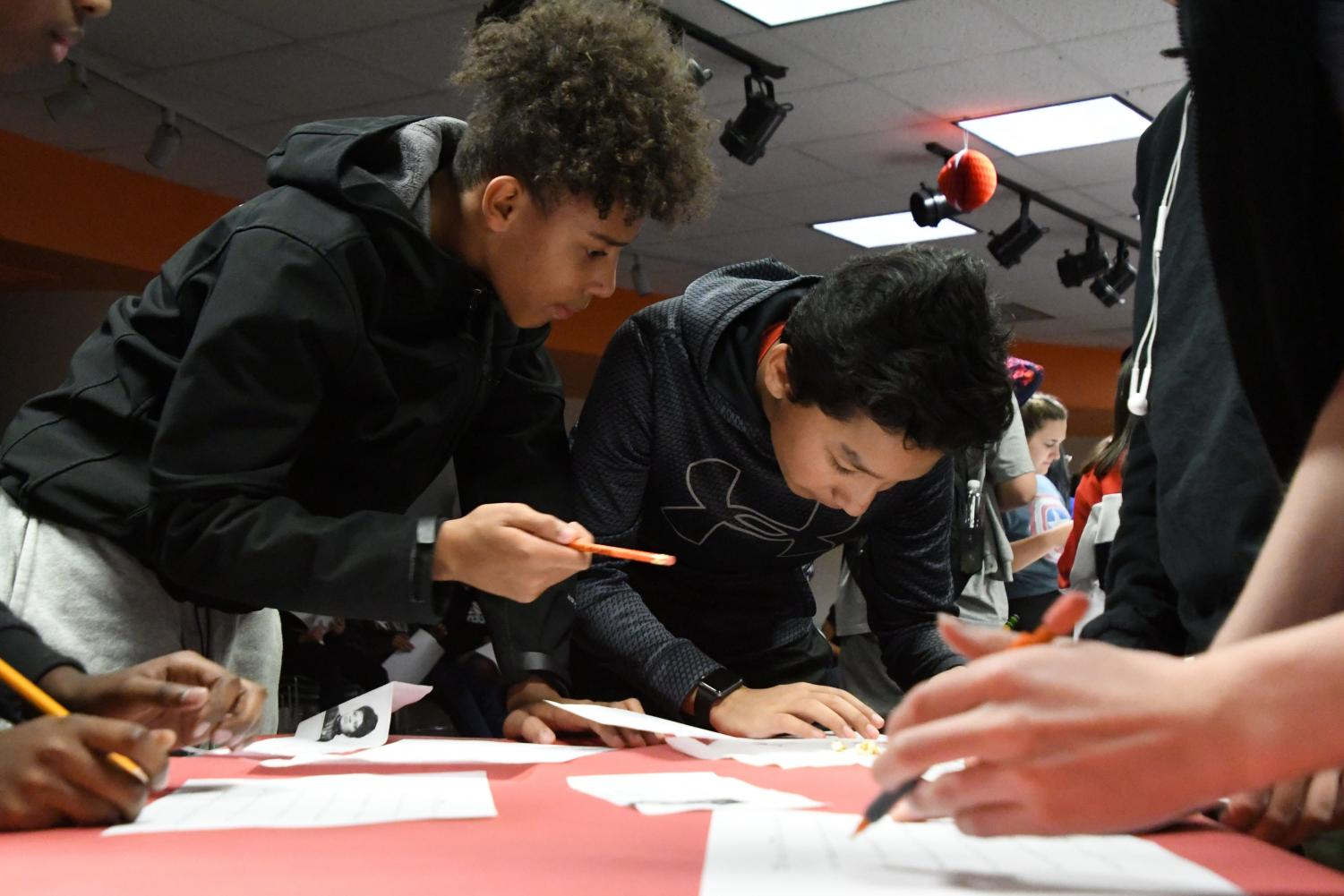 Freshman students help each other fill out their bingo boards during an activity during their social studies class in C350 Nov. 6.